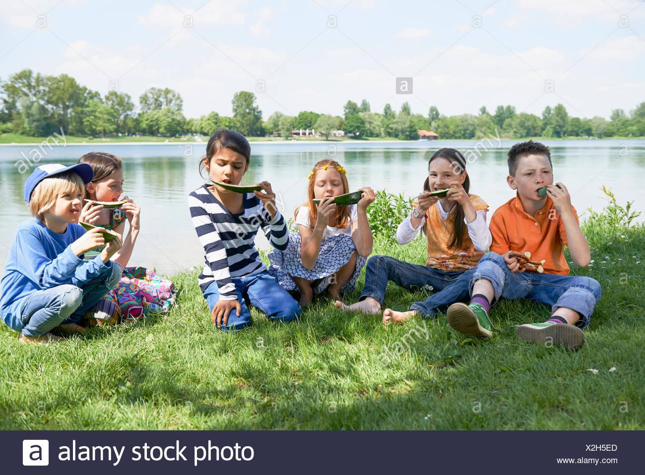 Les enfants profiter de tranches de melon au picnic, Munich, Bavière, Allemagne Photo Stock