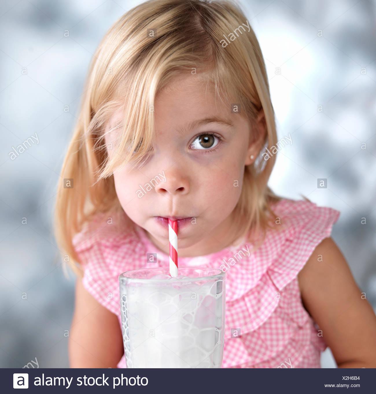 Portrait of young woman blowing bubbles dans le lait par l'intermédiaire de paille Banque D'Images