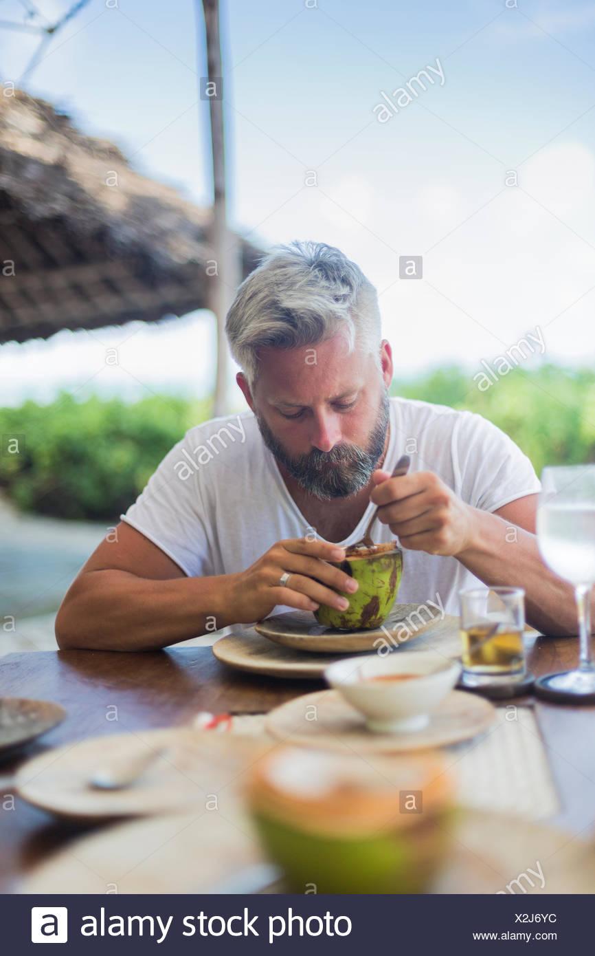Mid adult man eating watermelon à Diani Beach, Kenya Photo Stock