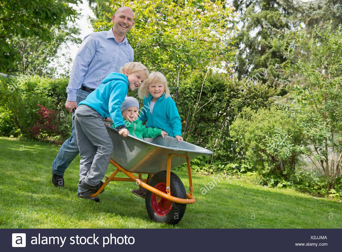 Père en poussant une brouette dans le jardin enfants Banque D'Images