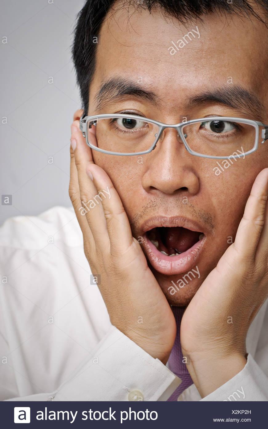 L'homme d'affaires à maturité avec l'excitation et bouche ouverte, closeup portrait of Asian. Photo Stock