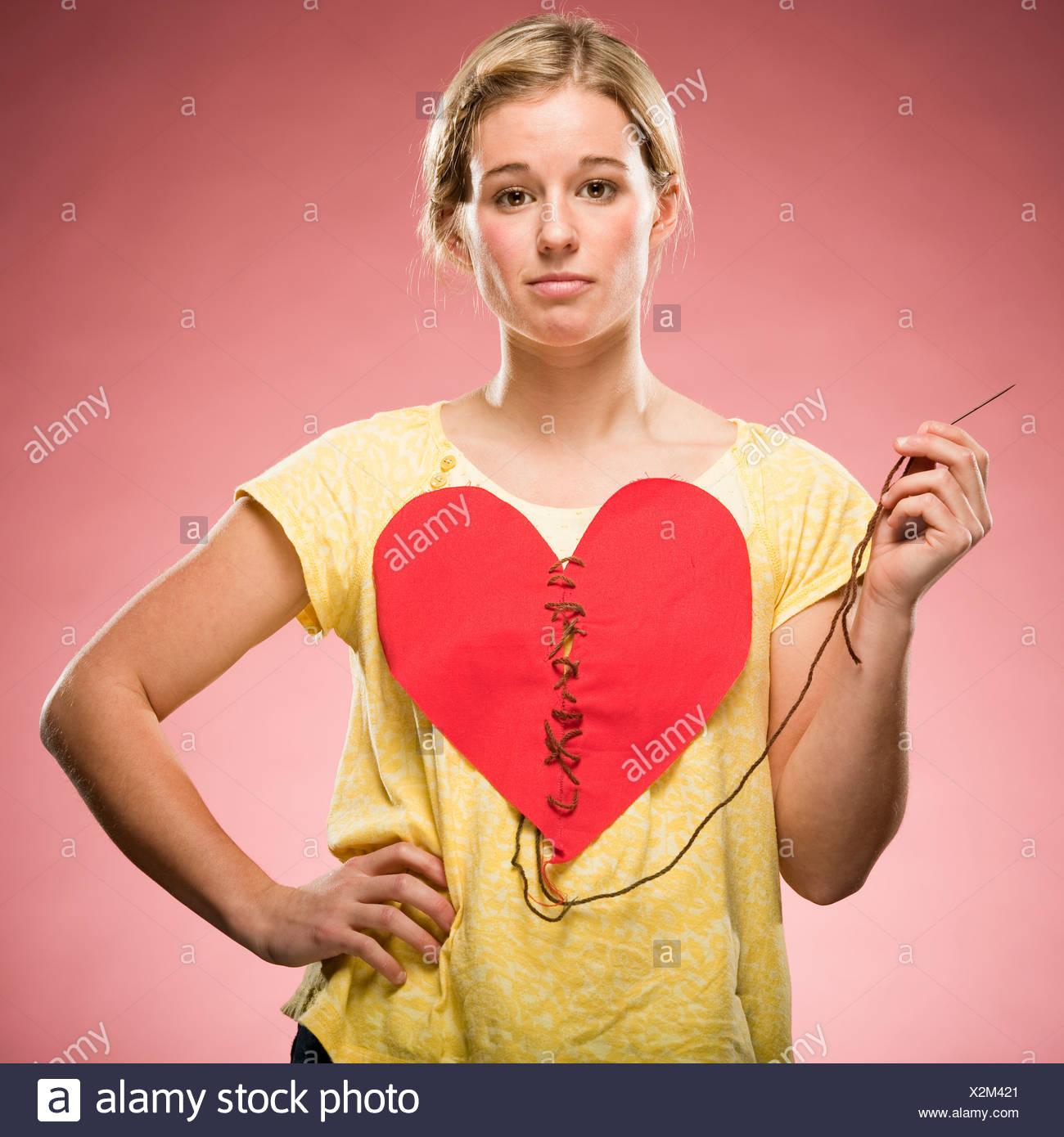 Femme cousant son propre coeur Photo Stock