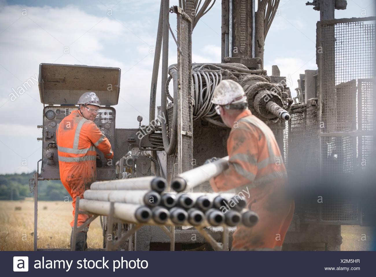 Les travailleurs dans les casques de forage d'exploitation Photo Stock