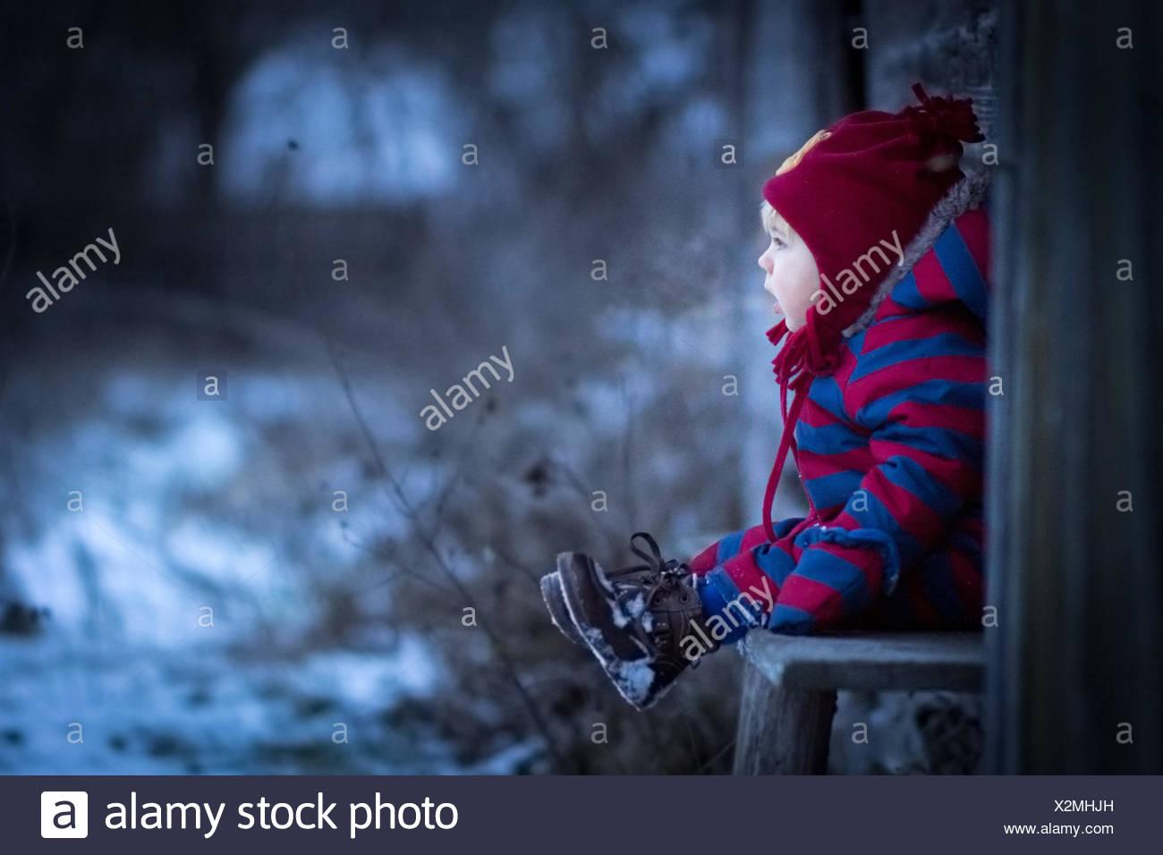 Jeune garçon assis sur un banc à l'extérieur Photo Stock