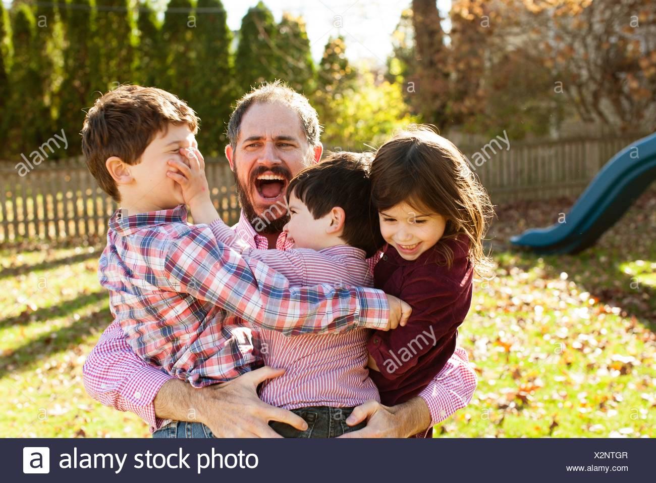 Père transportant les enfants ludique dans ses bras, la bouche ouverte à la surprise Photo Stock