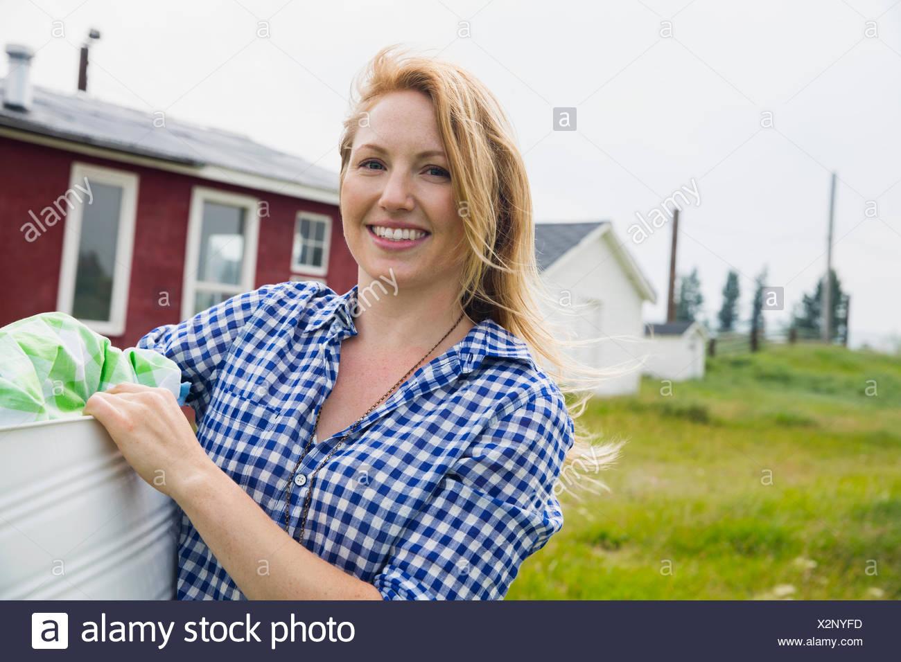 Portrait of smiling woman holding blanchisserie extérieur chambre Photo Stock