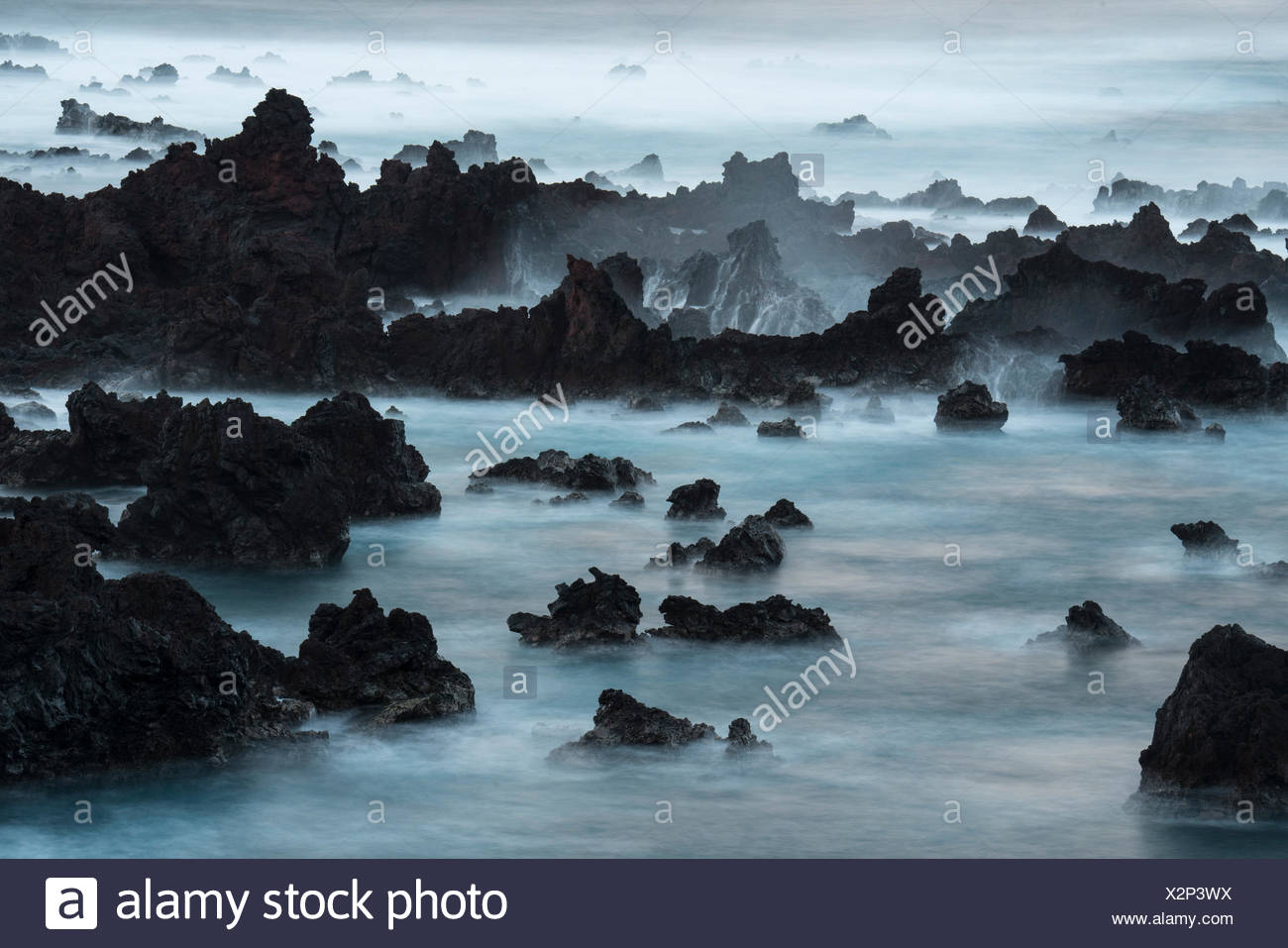 Une longue exposition de surfer sur des roches de lave à l'île de Pâques. Photo Stock
