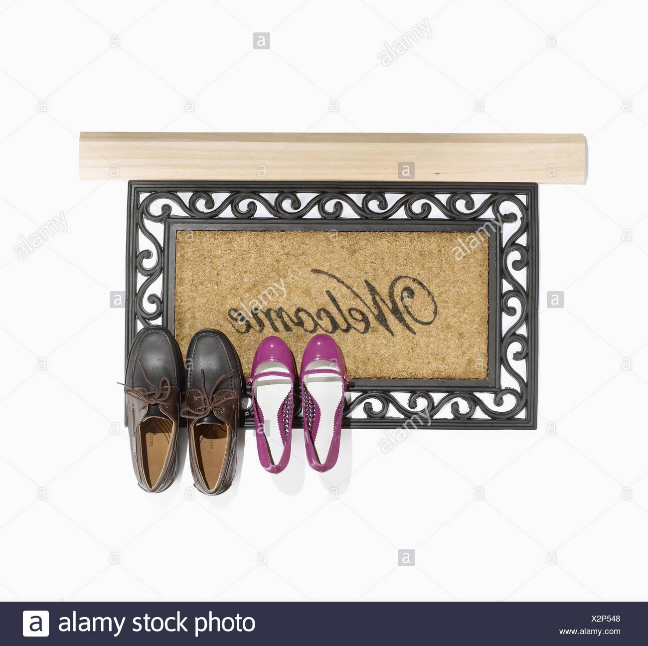 Tapis d'accueil avec deux paires de chaussures. Photo Stock