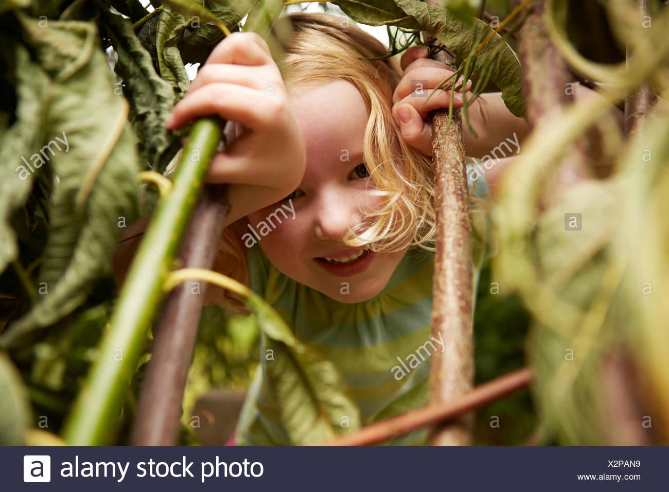 Close up portrait of girl se cachant dans des buissons Photo Stock