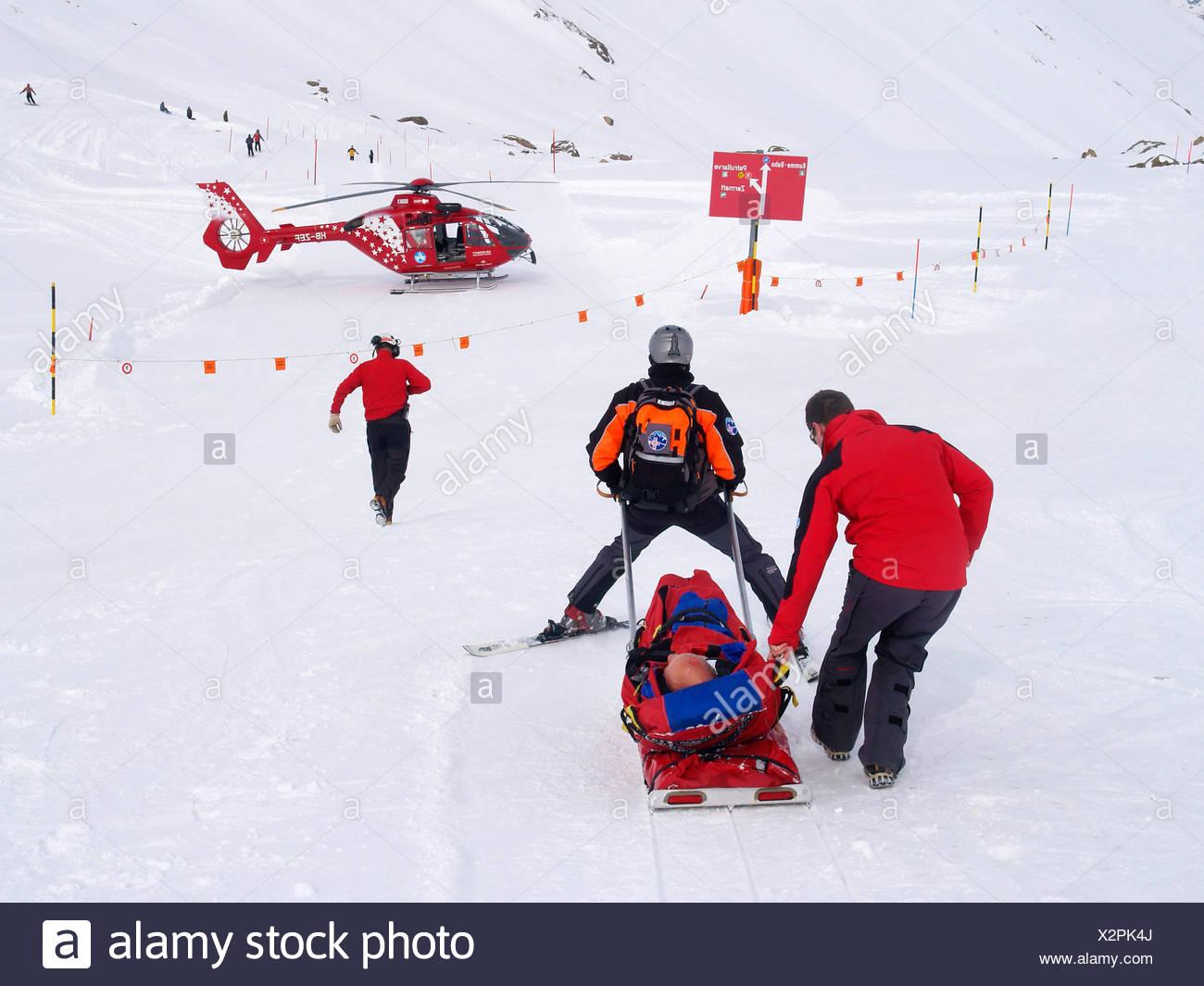 Le personnel de sauvetage aide un skieur blessé dans le domaine skiable de Zermatt dans les Alpes suisses. Photo Stock