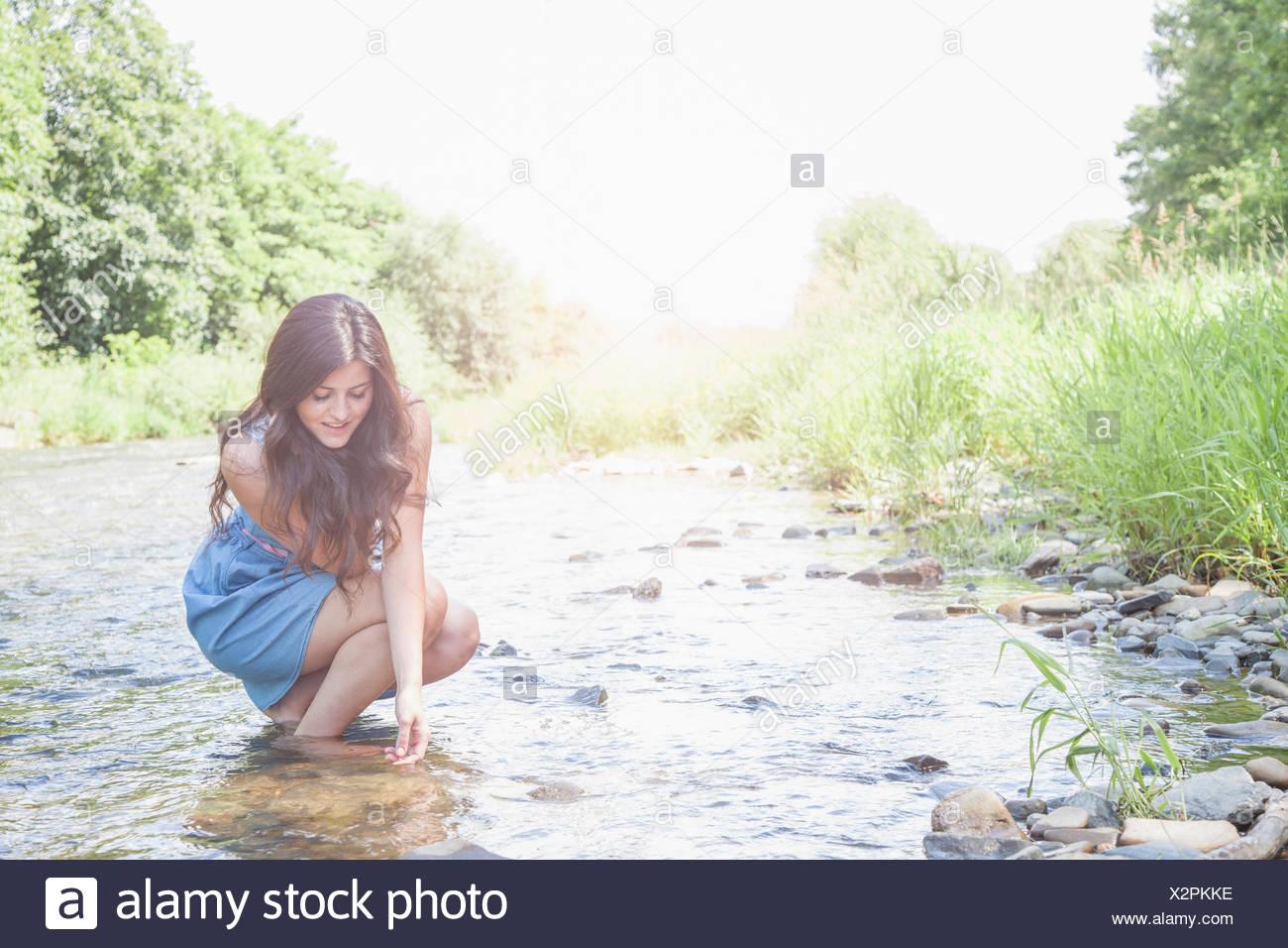 Jeune femme en cours d'eau peu profonde Photo Stock