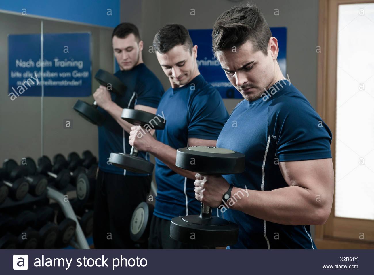 Trois jeunes hommes faisant la formation de poids dans une salle de sport Photo Stock