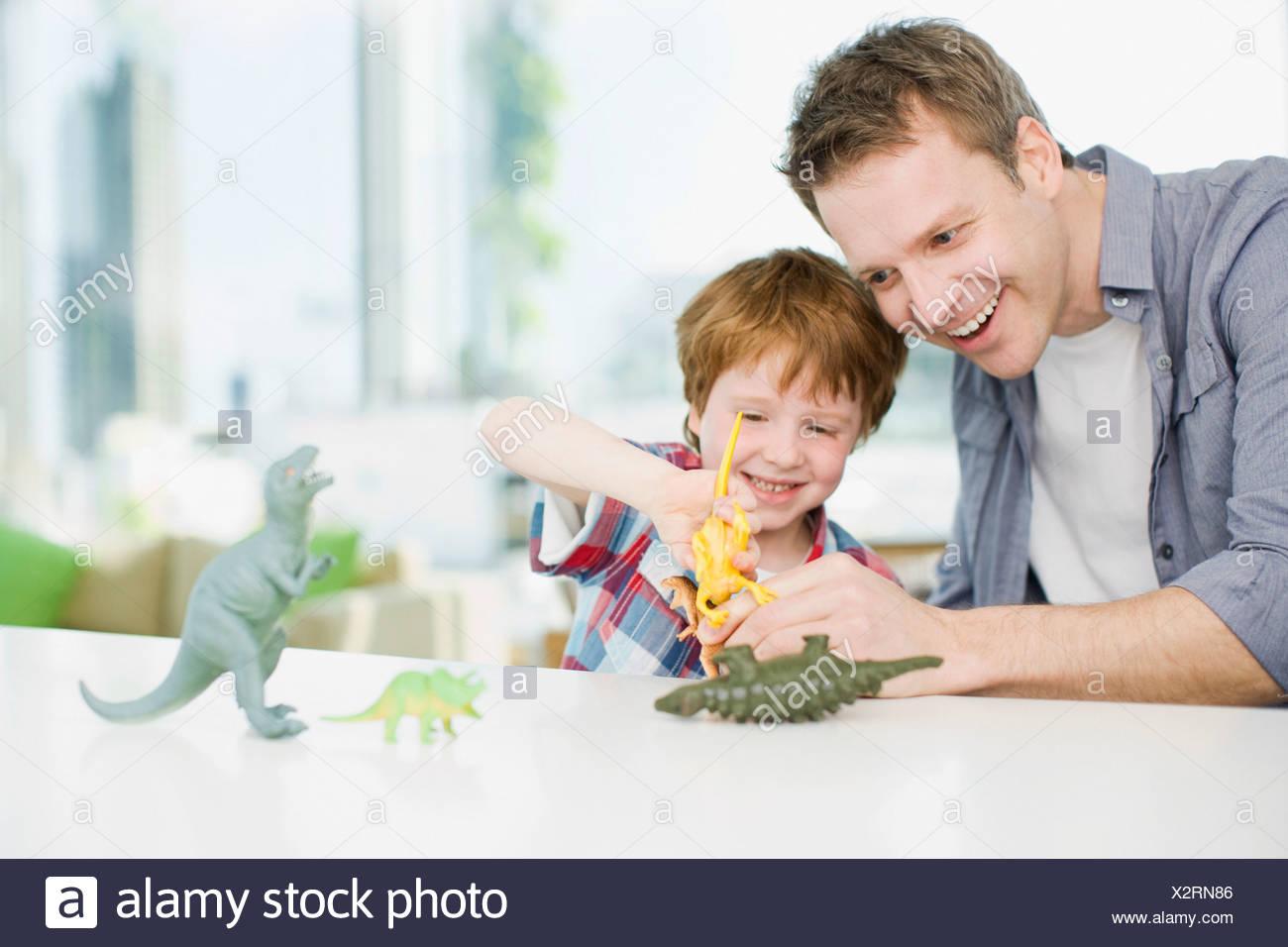 Père et fils jouant avec les dinosaures en plastique Photo Stock