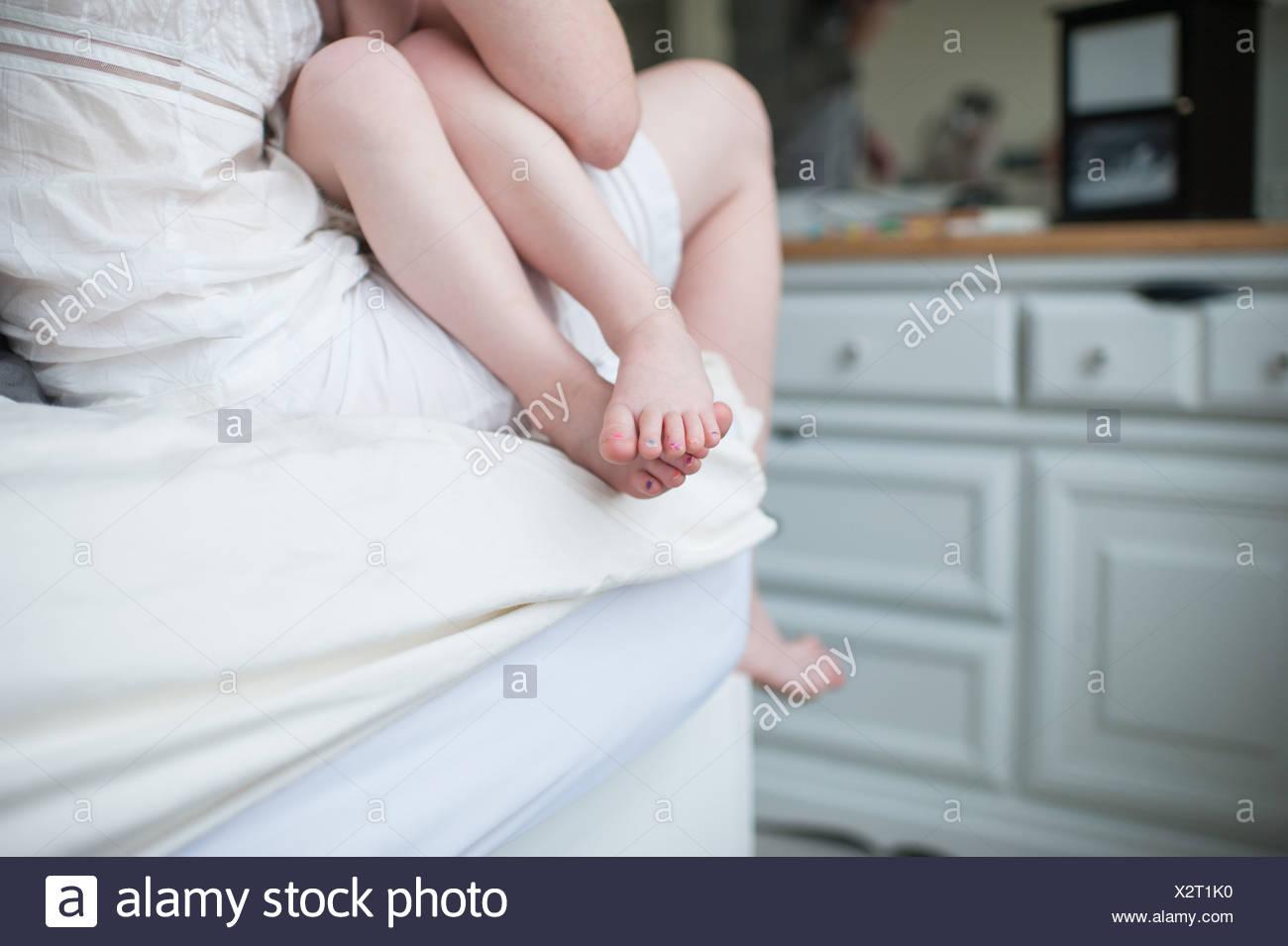 Fille assise sur mère, recadré composition des jambes nues et les pieds Photo Stock