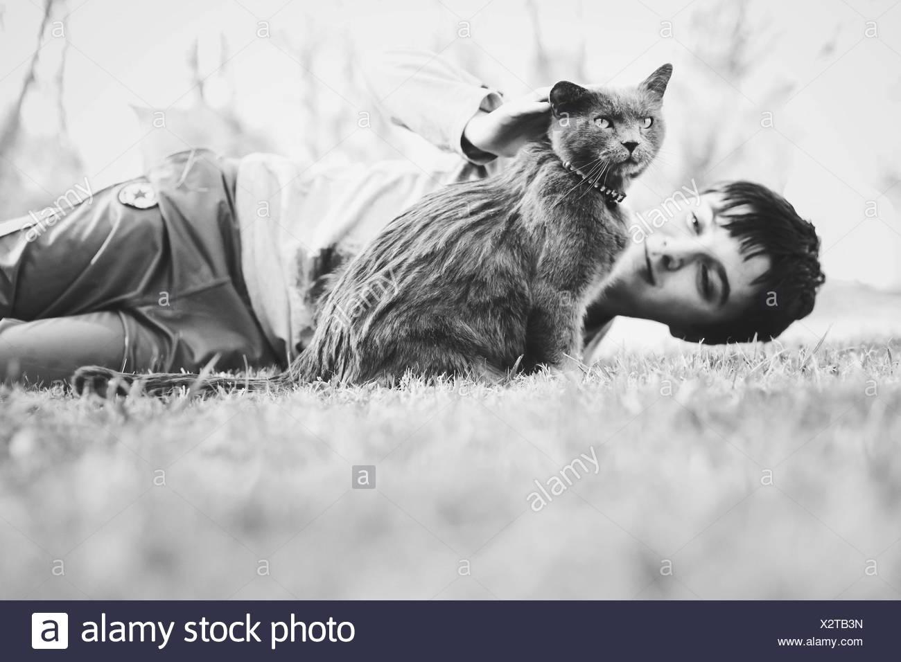 Garçon couché sur le terrain herbeux avec Cat Photo Stock