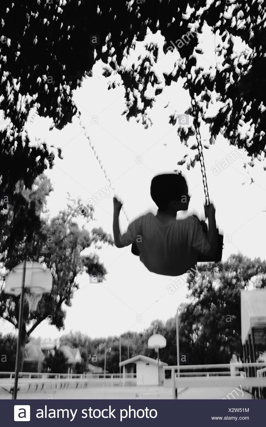 Blurred Motion de garçon bénéficiant sur Swing en aire de jeux Photo Stock