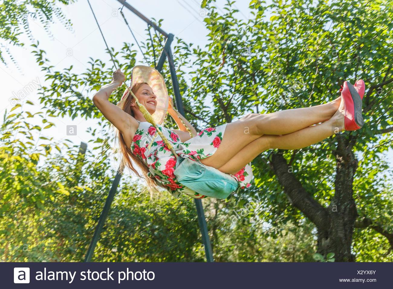 Mid adult woman swinging sur garden swing, low angle view Photo Stock