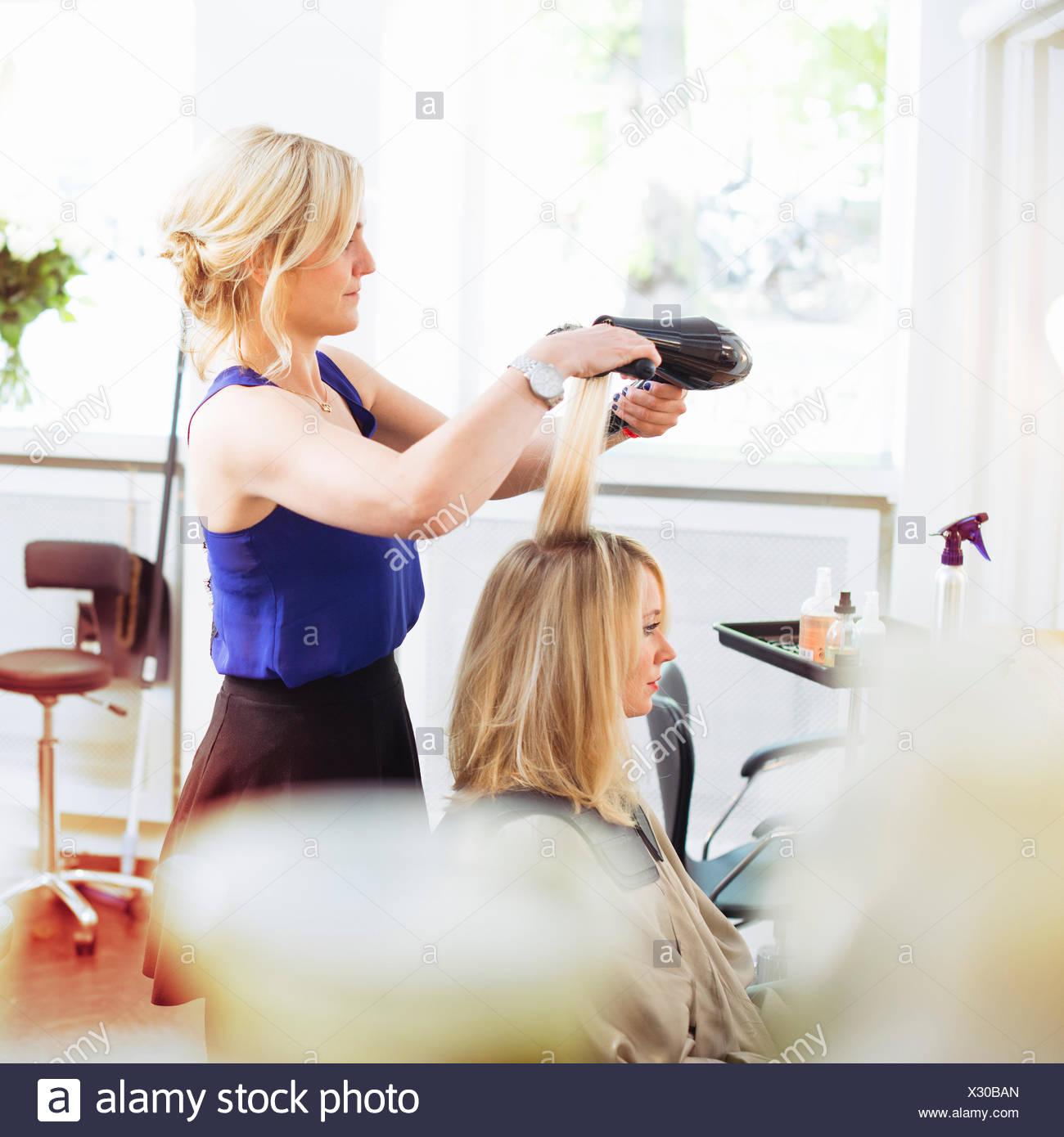 Coiffure cheveux du client de séchage avec un sèche-cheveux Photo Stock