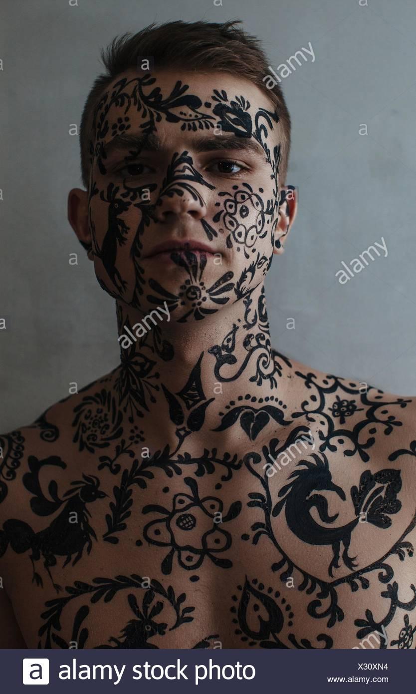 Portrait d'un homme torse nu avec body art sur son visage et corps Photo Stock