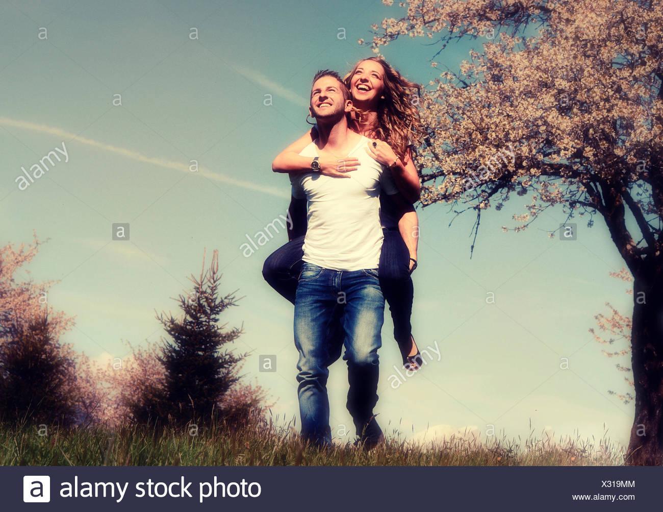 Homme portant une femme, souriant, en face d'un arbre en fleurs au printemps, Tyrol, Autriche Photo Stock