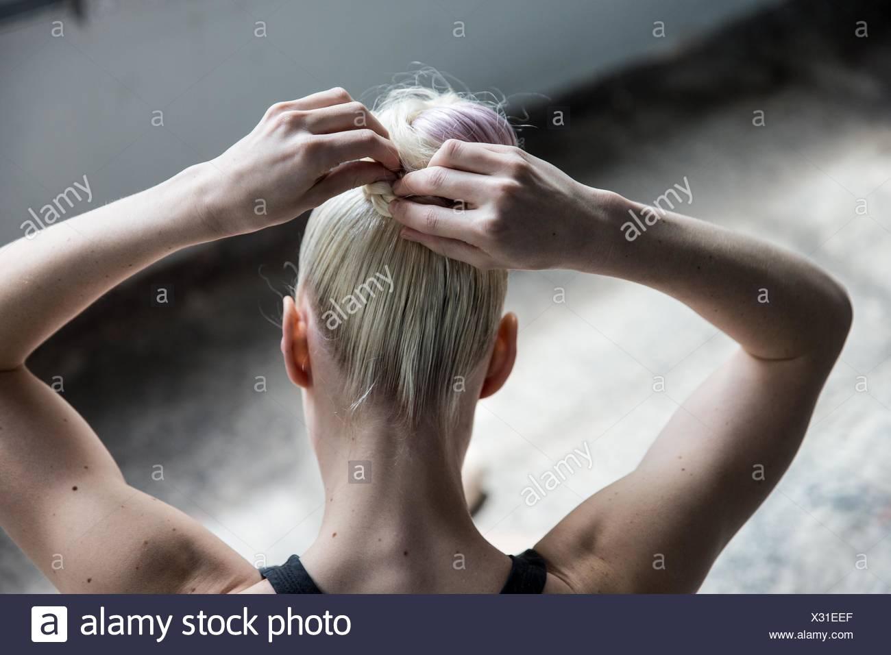 Femme d'attacher les cheveux en studio Photo Stock