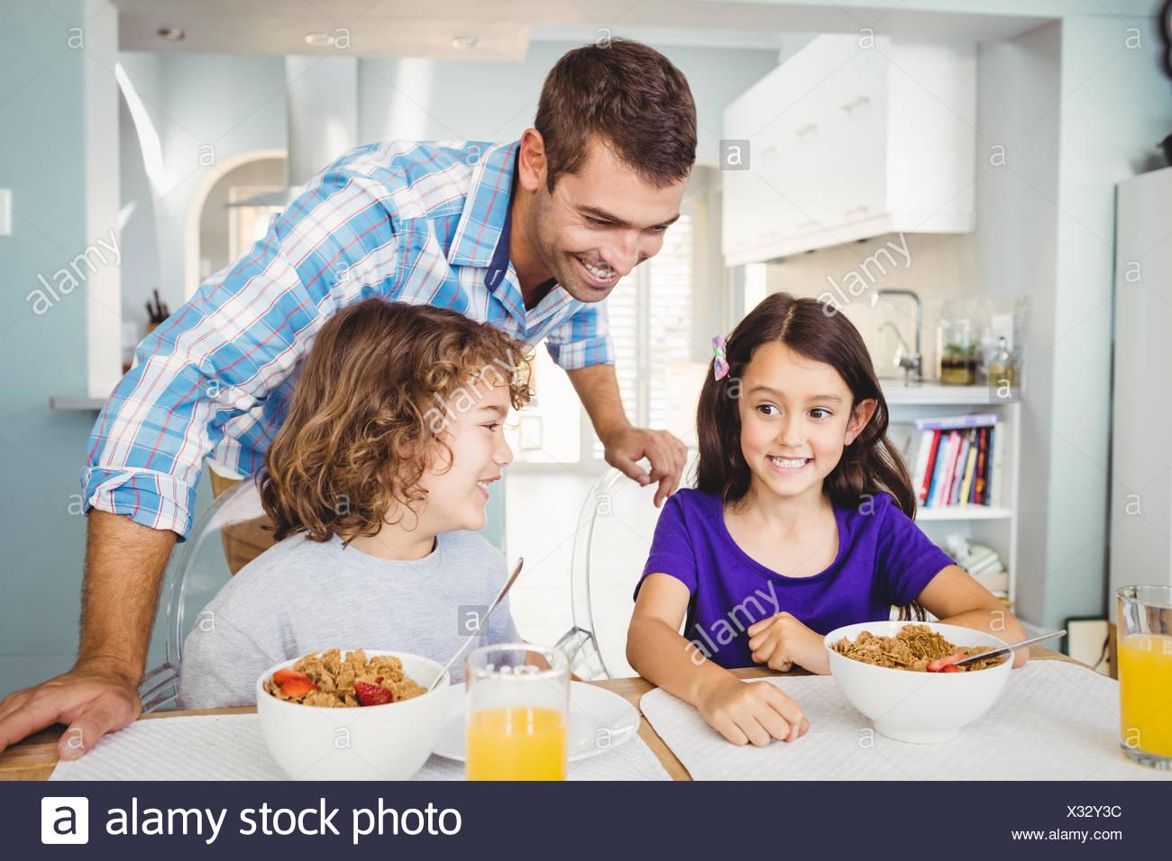 Homme heureux avec des enfants ayant le petit déjeuner Photo Stock