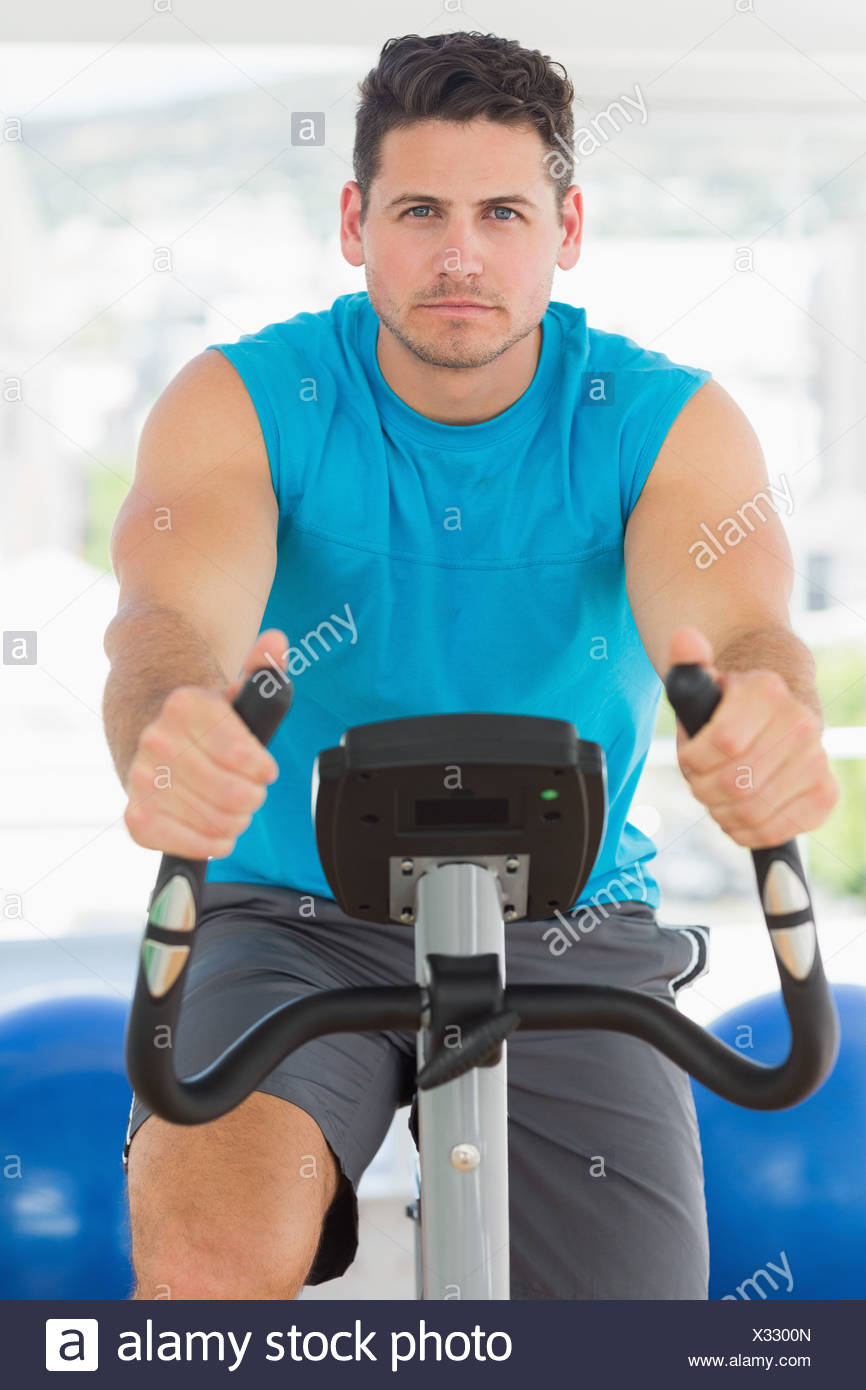 Young man working out at spinning class Photo Stock