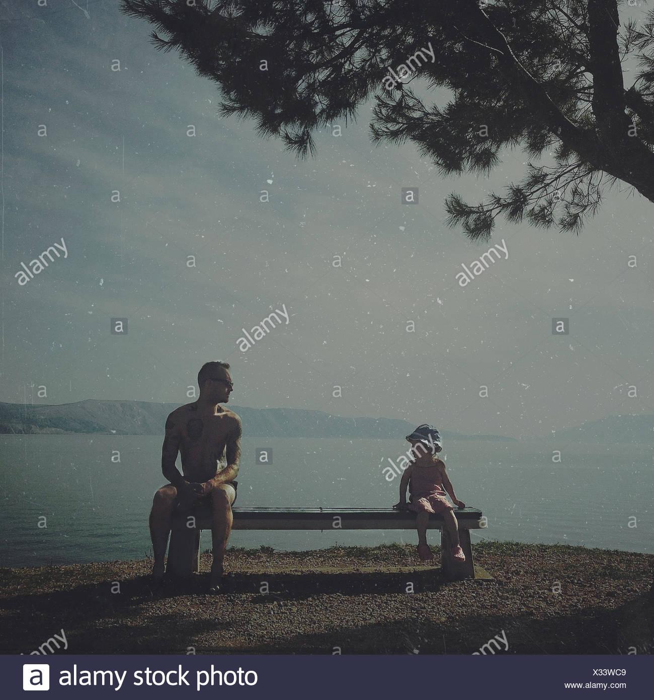 La Croatie, père et fille (2-3) sitting on bench par mer Photo Stock