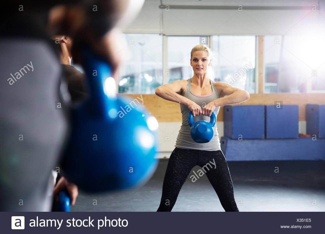 Les hommes et les femmes qui suivent une formation dans une salle de sport avec kettlebells Photo Stock
