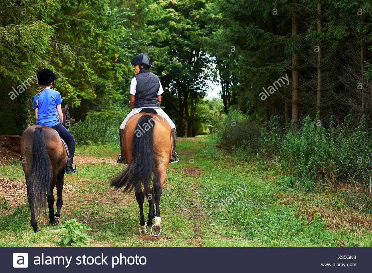 Vue arrière du mature woman and girl équitation Photo Stock