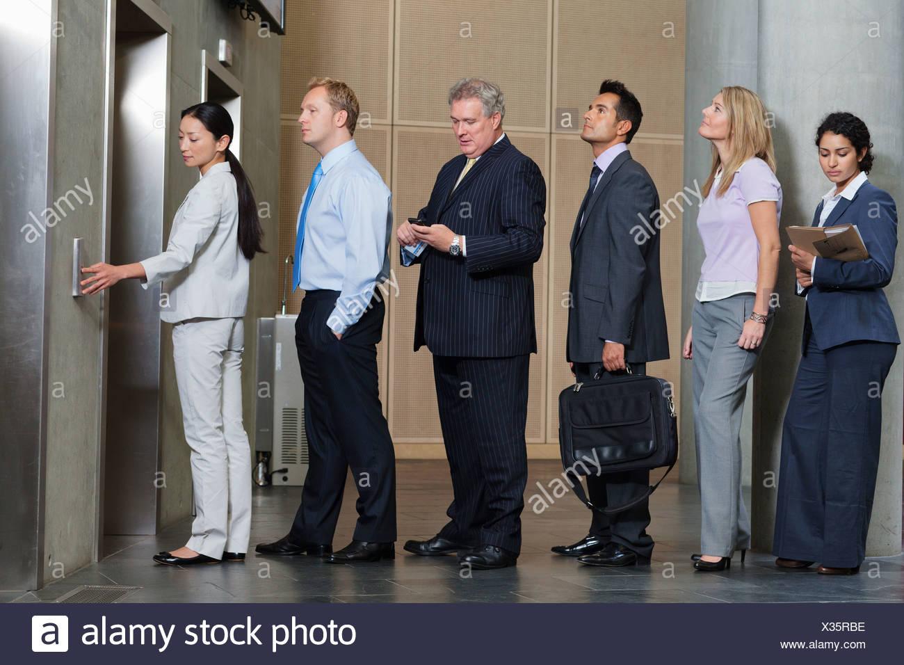 D'affaires en attente dans la file d'attente pour l'ascenseur Photo Stock