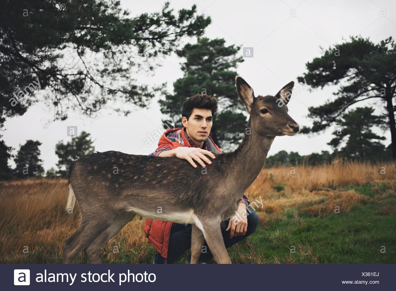Jeune homme accroupi dans le champ de flatter un deer Photo Stock