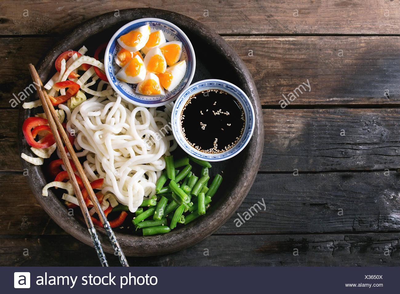 Ingrédients pour la cuisson faire revenir les nouilles Udon, haricots verts, tranchés paprika, œufs durs, de la sauce de soja avec les graines de sésame dans des bols en bois traditionnel avec Banque D'Images
