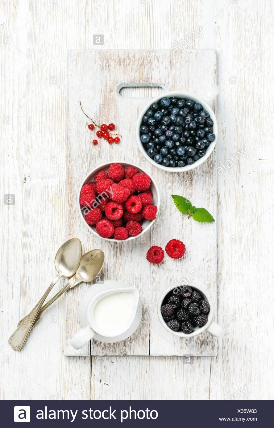 Framboises, mûres et myrtilles dans des bols servi avec de la menthe fraîche, de groseille rouge et de lait sur bois peint blanc backgroun Photo Stock