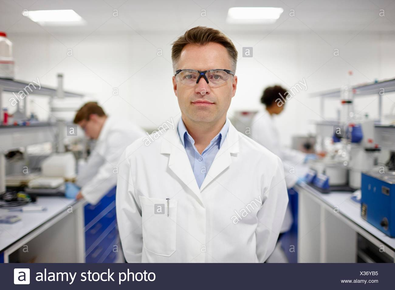 Scientist in laboratory, des collègues qui travaillent en arrière-plan Photo Stock
