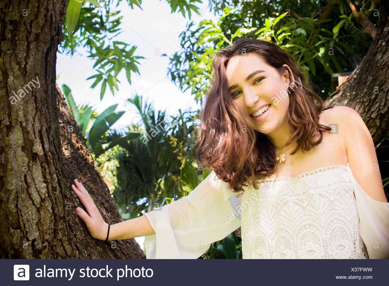 Portrait of teenage girl climbing tree Banque D'Images