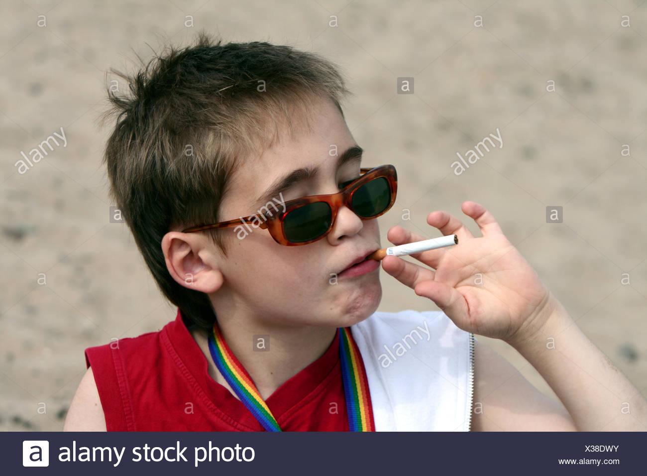 10 ans cool garçon avec des lunettes de soleil et la cigarette Photo Stock e41f5c5a8c61