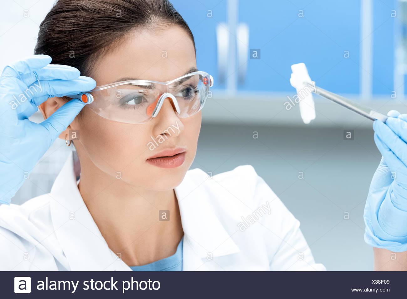 Portrait de chercheur scientifique à des lunettes et des gants à  l échantillon de produits ded7b2eef6e5