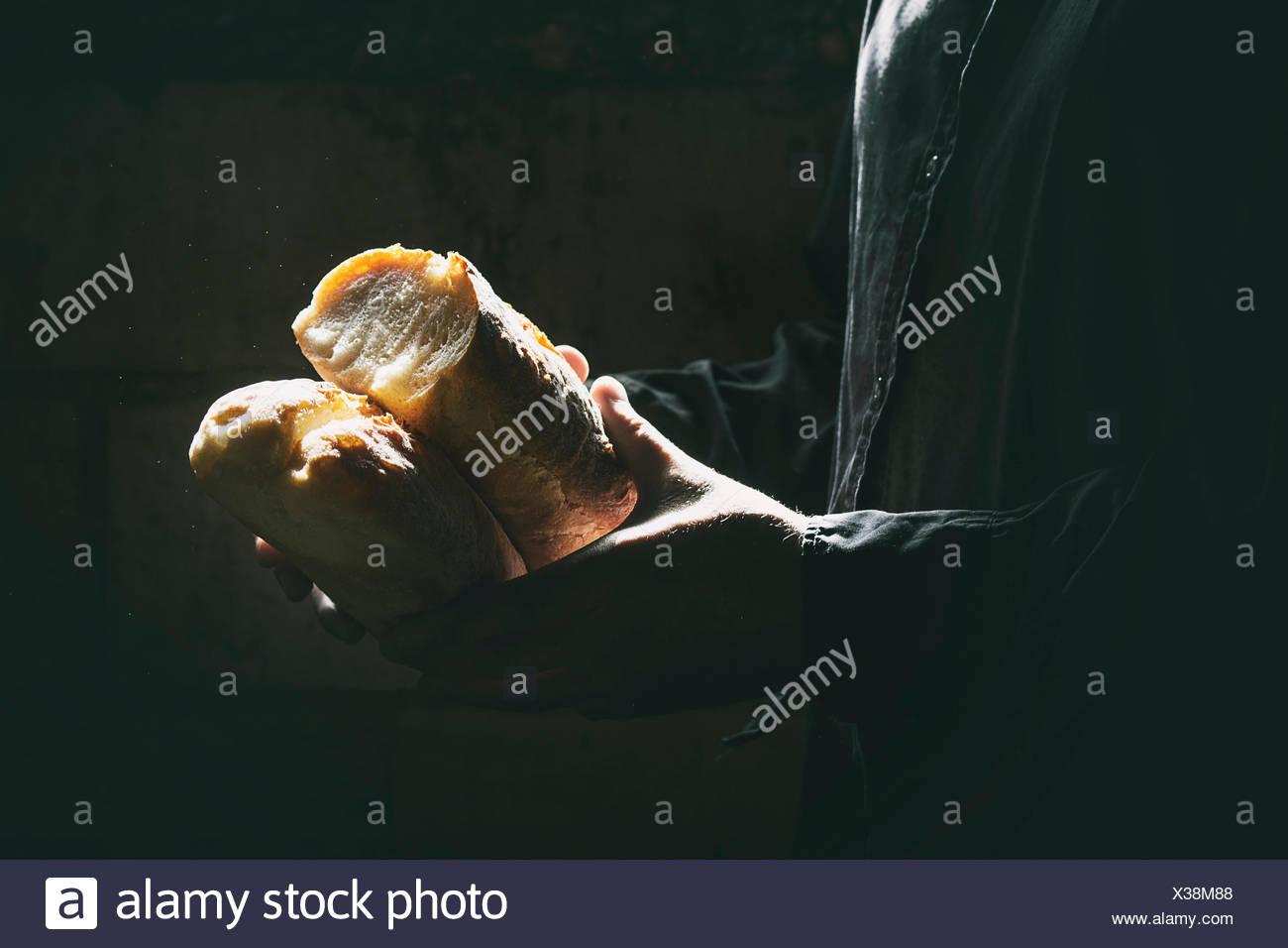 Miche de pain de blé frais entre les mains de l'homme dans le soleil. Lumière jour rustique dans une pièce sombre. Photo Stock