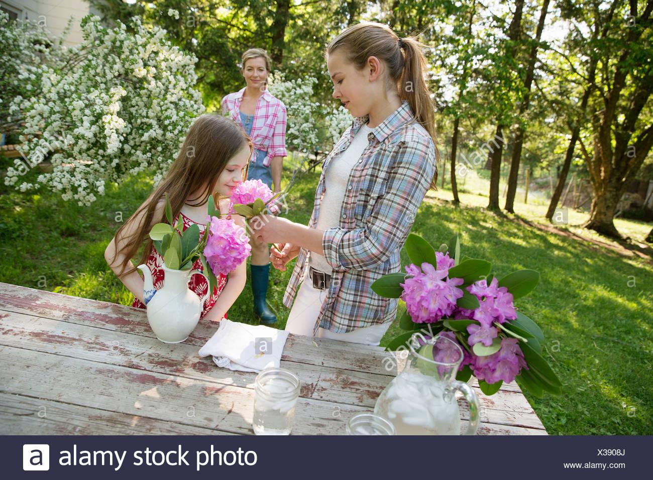 Trois personnes des fleurs et les disposer ensemble. Une femme mature, un adolescent et un enfant. Photo Stock