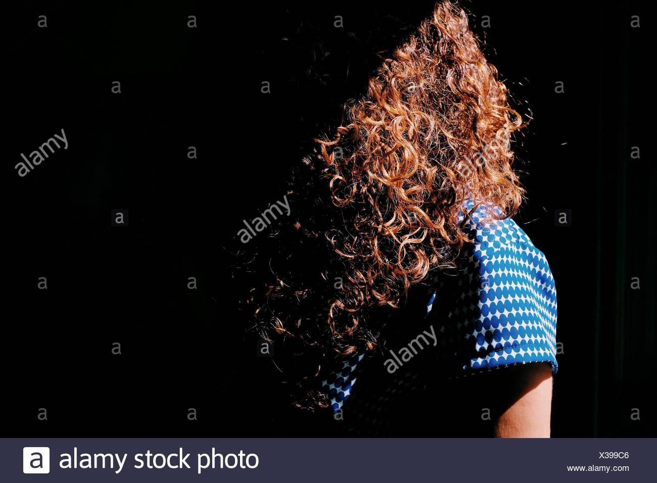 Femme aux cheveux bruns bouclés à la lumière du soleil Photo Stock