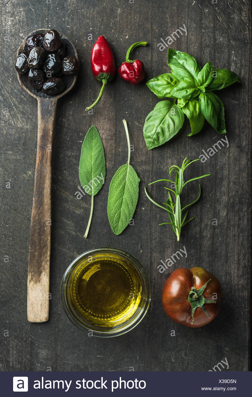 Légumes et herbes sur fond rustique en bois sombre. Olives noires grecques, frais vert sauge, romarin, basilic, fines herbes, tomate, huile Photo Stock