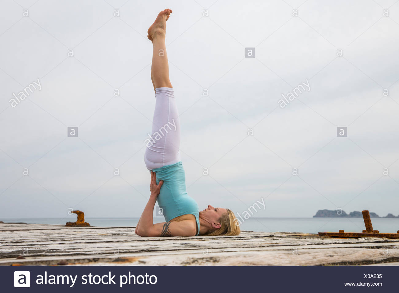 Mid adult woman avec jambes soulevées practicing yoga on wooden pier mer Photo Stock