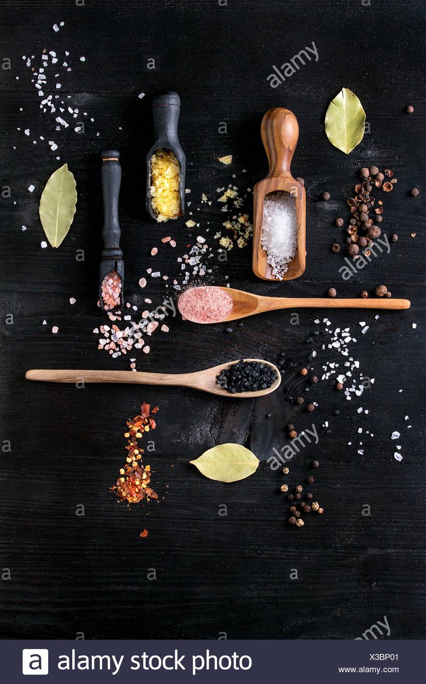 Variété de sel coloré de safran jaune, rose, noir, blanc de l'Himalaya et la fleur de sel de mer dans des cuillères en bois avec black, piment, piment de pepp Photo Stock