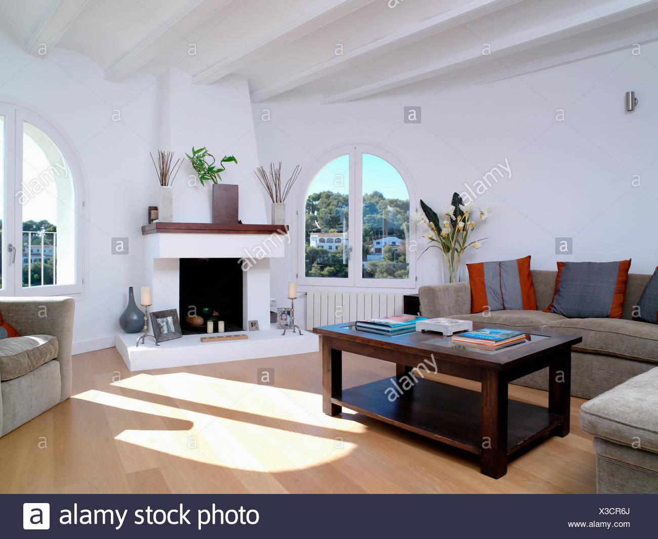 Entre Cheminée Moderne Dans Des Fenêtres En Arche Côtière Blanc Salon Avec  Table Basse En Bois Sombre Et De Parquet En Bois Clair.
