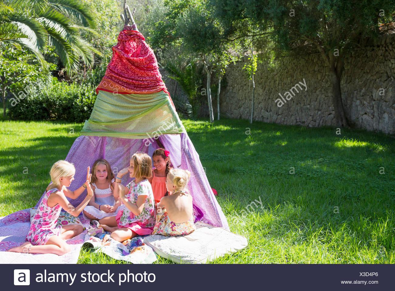 Cinq jeunes filles, jouant des mains jeux en face de tipi Photo Stock