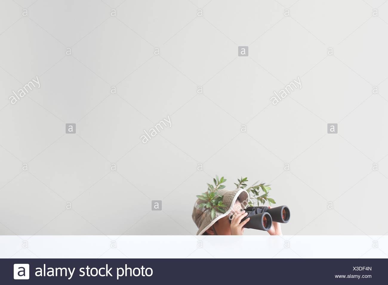 Boy looking through binoculars avec quelques feuilles et branches d'arbre coincé sur son safari hat Photo Stock