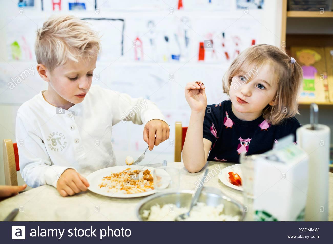 Les élèves du primaire ayant l'alimentation en maternelle Photo Stock