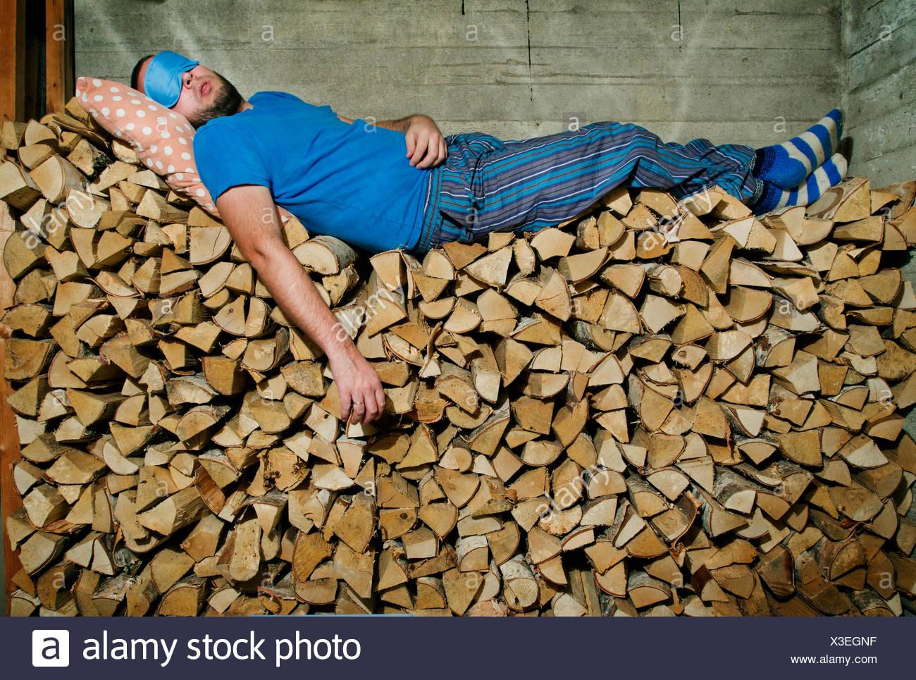 La Finlande, Heinola, Man sleeping on pile de bois de chauffage Photo Stock