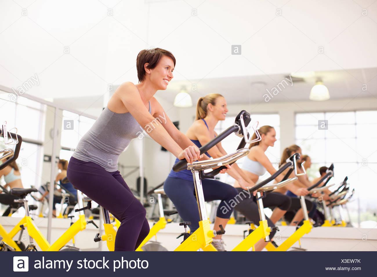Portrait of smiling women sur des vélos d'exercice dans un gymnase Photo Stock